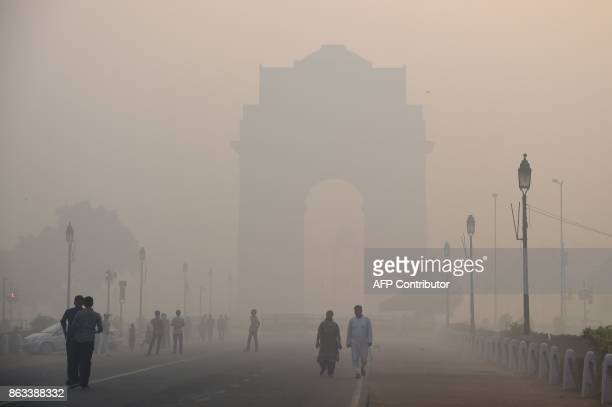 Indian pedestrians walking near the India Gate monument amid heavy smog in New Delhi on October 20 the day after the Diwali Festival New Delhi was...