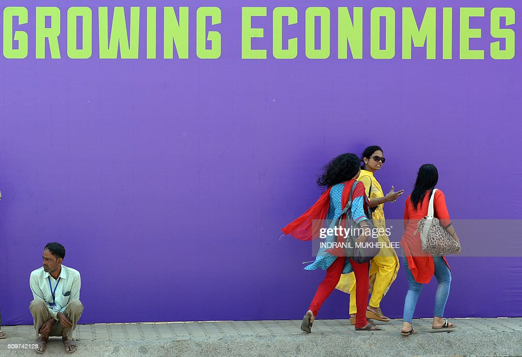 Indian pedestrians walks past a sign at the venue for the 'Make in India Week' in Mumbai on February 12, 2016. Over 190 companies, and 5,000 delegates from 60 countries, are due to take part in the first 'Make in India' week to be held in Mumbai from February 13-18. AFP PHOTO / INDRANIL MUKHERJEE / AFP / INDRANIL MUKHERJEE