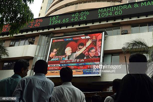 Indian pedestrians watch as a digital broadcast presents the rolling share price information and national election results news coverage on the...