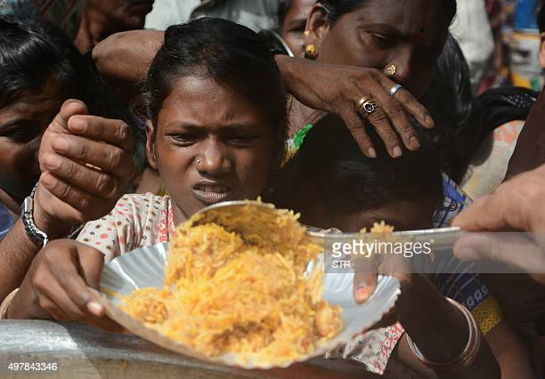 Indian people collect food from a distribution point after flooding in Chennai on November 19 2015 Large areas of the southern Indian city of Chennai...