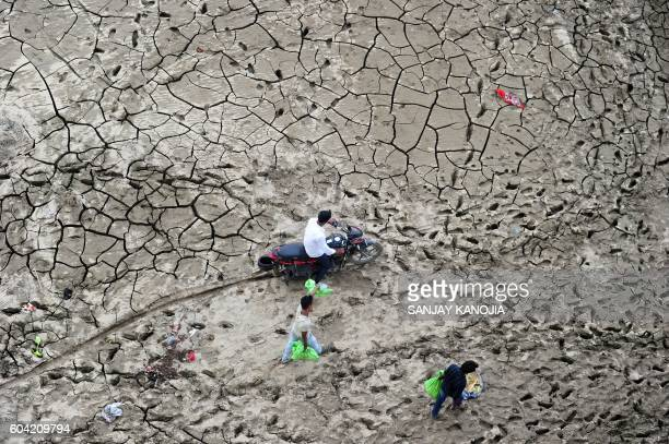 TOPSHOT Indian people cross marshland area on the bank of river Yaumna after flood waters receded at the Sangam area in Allahabad on September 13...