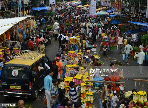 Indian people crowd gather at the flower and vegetable market as normal life returns in Mumbai on August 30 after heavy rains brought major flooding...