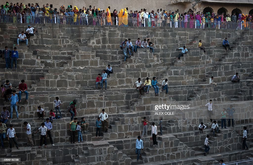Indian people gather at the historic chand baori stepwell in abhaneri