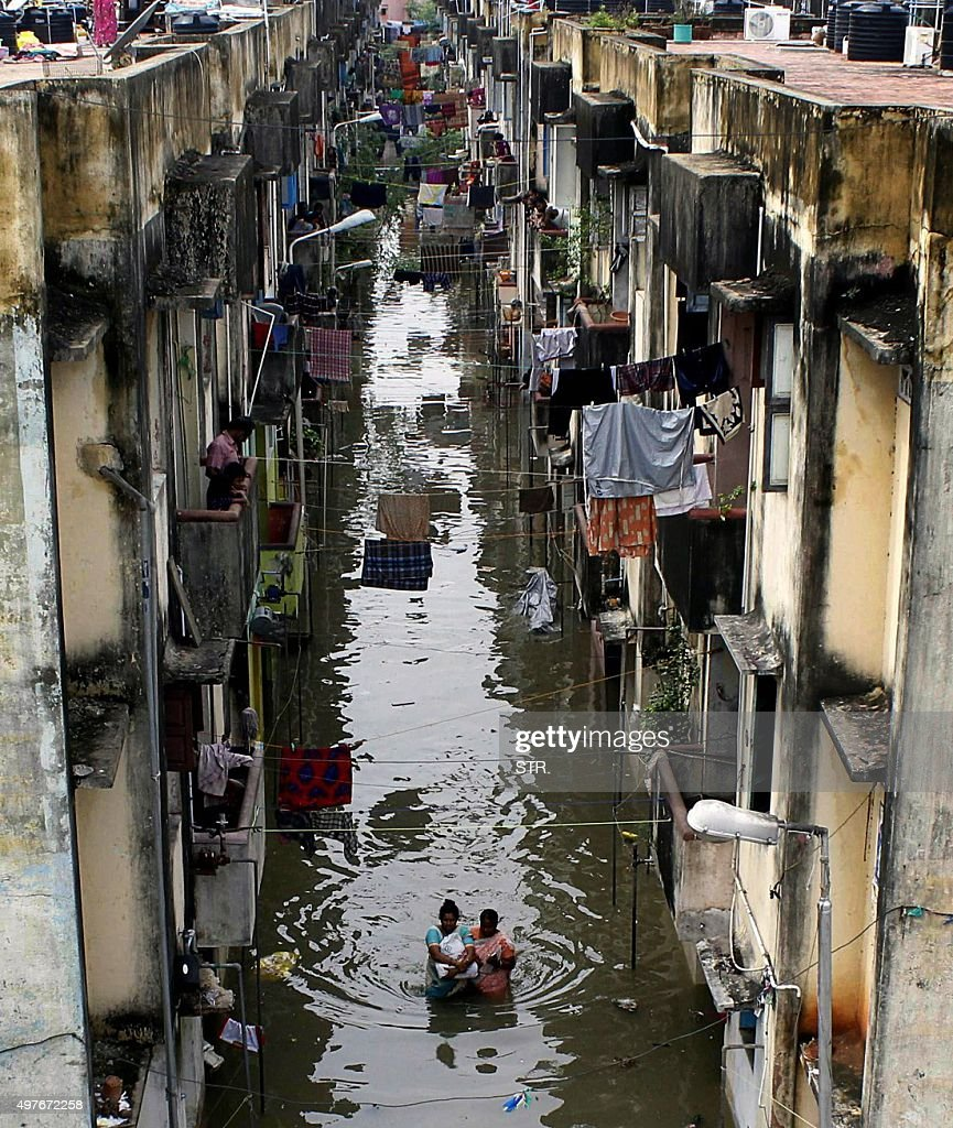 Indian people gather on top and below of a residential area flooded after heavy rains in Chennai on November 18 2015 Large areas of the southern...
