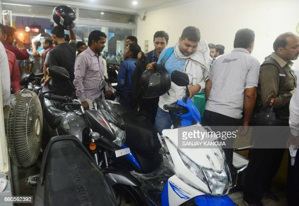 Indian people gather to purchase scooters and motorcycles at an automobile showroom as companies dispose of BS3 emission standard vehicle at a heavy...