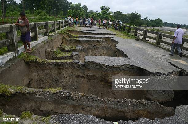 TOPSHOT Indian people look at a bridge damaged by torrential rain at Toribari village on the outskirts of Siliguri on July 212016 Continuous rainfall...