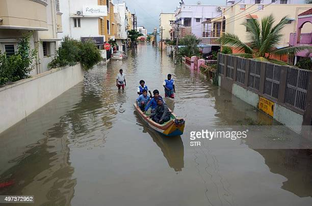 Indian people make their way in a canoe on a flooded street following heavy rain in Chennai on November 16 2015 Large areas of the southern Indian...