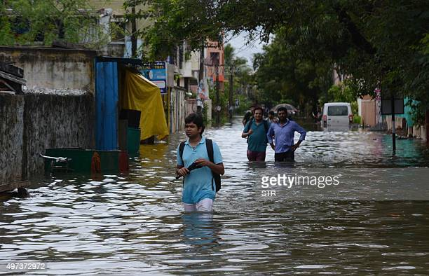 Indian people make their way on a flooded street following heavy rain in Chennai on November 16 2015 Large areas of the southern Indian city of...