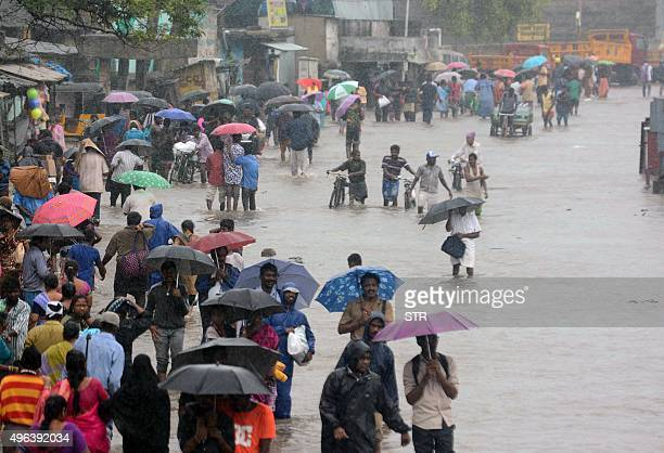 Indian people make their way on a flooded street in Chennai on November 9 2015 following heavy rain from an approaching cyclonic system off the coast...