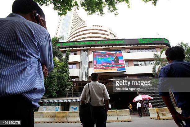 Indian people outside Bombay Stock Exchange building in Mumbai follow the raised exchange rate after Narendra Modi has won a seat in India's old...