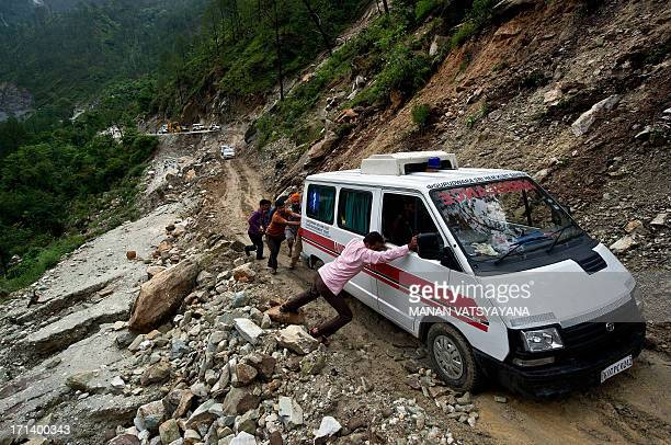Indian people push an ambulance through a damaged section of the road caused by overnight rains in Gauchar on June 24 2013 Indian priests are...