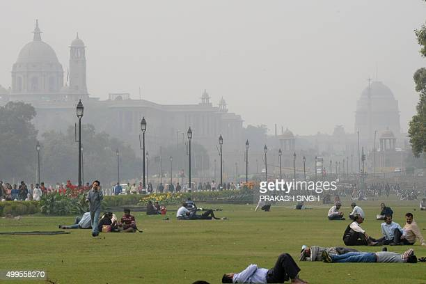 Indian people relax on the lawns near smog enveloped government offices on Rajpath in New Delhi on December 2 2015 AFP PHOTO/ Prakash SINGH / AFP /...