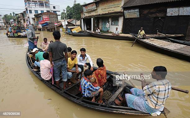 Indian people sit on a boat on a flooded road in Ghatal some 95 kms south of Kolkata on August 4 2015 Floods from days of torrential rain have now...