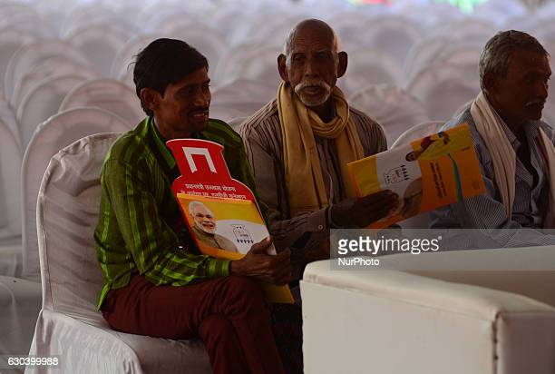 Indian people sit on chairs holding free gas connection cards given by Minister of state for Patrolium and natural gas Mr Dharmendra Pradhan on the...