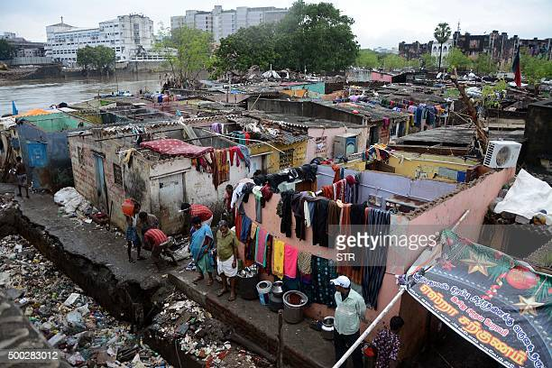 Indian people sort through their possessions next to damaged homes as floodwaters recede in Chennai on December 6 2015 Residents in India's southern...