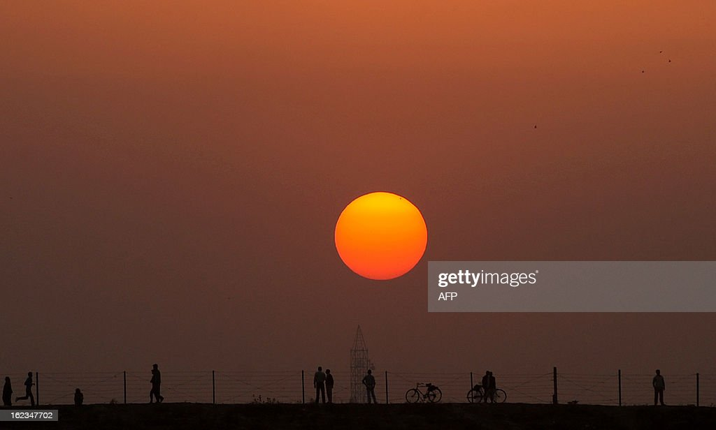 Indian people stand near Sangam, the confluence of the Yamuna, Ganges and mythical Saraswati rivers and the site of the Kumbh Mela in Allahabad on February 22, 2013. AFP PHOTO/ SANJAY KANOJIA