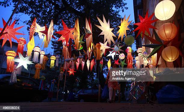 Indian people stand next to lanterns displayed at a roadside on the eve of Diwali the Hindu festival of lights in Mumbai India on November 10 2015...