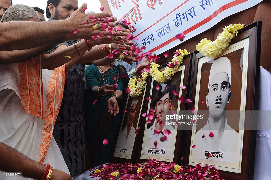 Indian people throw rose petals as they pay tribute to Indian freedom fighters Bhagat Singh, Rajguru and Sukhdev at the historical Jallian Wala Bagh in Amritsar on March 23, 2013. The freedom fighters were hung in Lahore prison on March 23, 1931 by the British for killing British police officer, J.P. Saunders, in 1928. AFP PHOTO/ NARINDER NANU