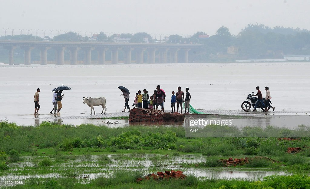 Indian people walk along a flooded road near Sangam, the confluence of the Ganges, Yamuna and mythical Saraswati rivers, as the water level of the Ganges and Yamuna rivers rises in Allahabad on July 1, 2013. Construction along river banks will be banned in the devastated north Indian state of Uttarakhand amid concerns unchecked development fuelled June's flash floods and landslides that killed thousands, the state's top official said July 1. AFP PHOTO/ SANJAY KANOJIA