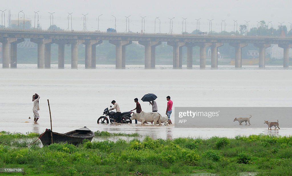 Indian people walk along a flooded road near Sangam, the confluence of the Ganges, Yamuna and mythical Saraswati rivers, as the water level of the Ganges and Yamuna rivers rises in Allahabad on July 1, 2013. Construction along river banks will be banned in the devastated north Indian state of Uttarakhand amid concerns unchecked development fuelled June's flash floods and landslides that killed thousands, the state's top official said July 1.