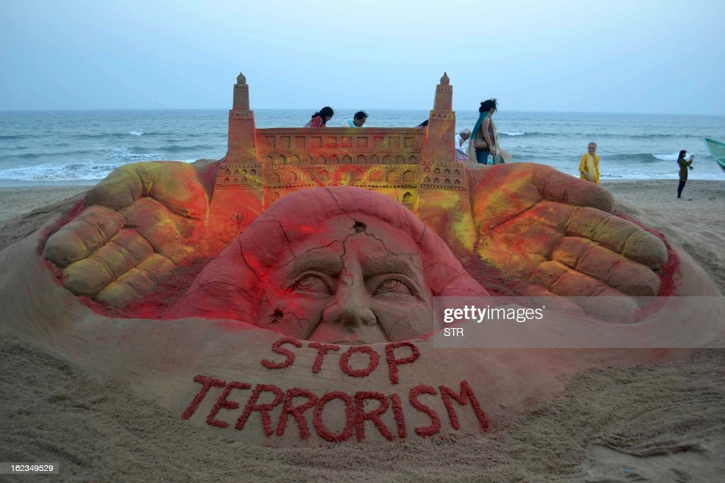 Indian people walk around a six foot sand sculpture on 'Stop Terrorism' created by sand artist Sudersan Pattnaik at Golden Sea beach Puri, about 65 kilometers from Bhubaneswar on February 22, 2013. Indian police revealed Friday they had been warned of a possible attack by Islamist militants in a bustling shopping area of Hyderabad where twin bombings killed at least 14 people and wounded scores.