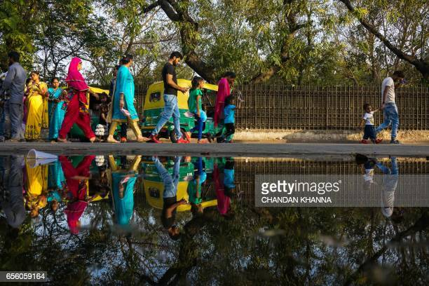 TOPSHOT Indian people walk by a puddle on a street in New Delhi on March 21 ahead of World Water Day World Water Day is marked annually on March 22...