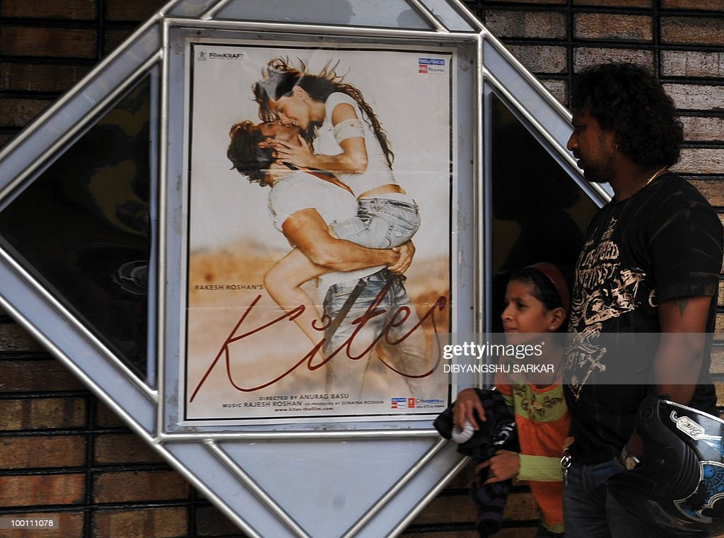 Indian people walk past an advertising board for the newly released Bollywood movie Kites in Bangalore on May 21, 2010. Kites has been banned for exhibition in the state of Karnataka by the Karnataka Film Chamber of Commerce (KFCC) for violating local industry norms. AFP PHOTO/Dibyangshu SARKAR