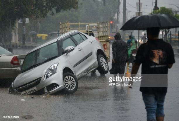 Indian people walk through rain next to a car that into a ditch on the side of a road in Amritsar on June 28 2017 / AFP PHOTO / NARINDER NANU