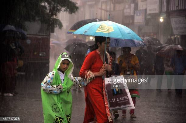 Indian people walk with umbrellas during a heavy rainfall in the northern hill town of Shimla on July 26 2014 Weather officials have said that the...
