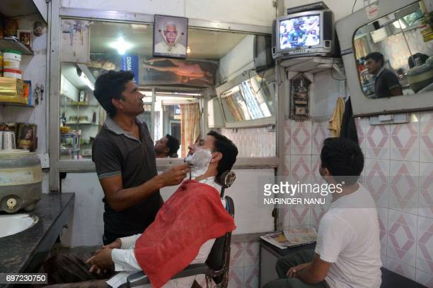 Indian people watch the IndiaPakistan cricket final match taking place in London at a barbershop in Amritsar on June 18 2017 The Champions Trophy...