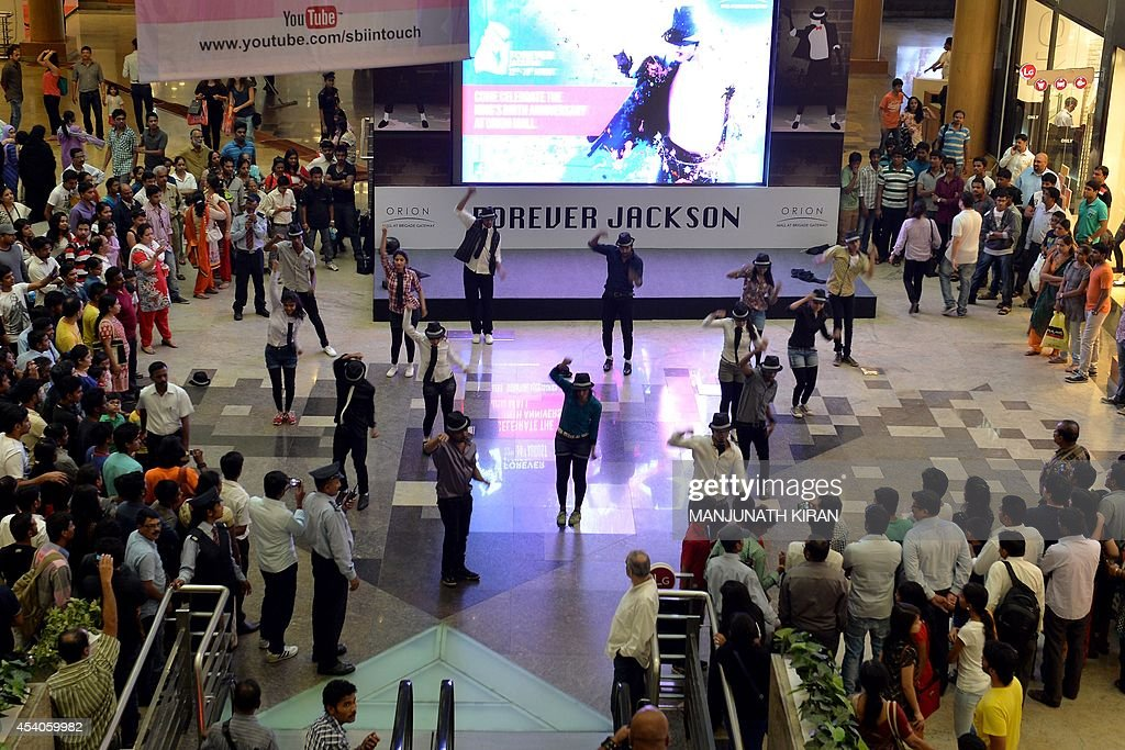 Indian performers dance to the music of late US pop star Michael Jackson at a commemorative exhibition, set up at the mall as part of birthday celebrations for the late music icon, in Bangalore on August 23, 2014. Fans of the lengendary pop star Michael Jackson, who passed away in 2009, are gearing up to celebrate what would have been his 56th birthday on August 29. AFP PHOTO/Manjunath KIRAN