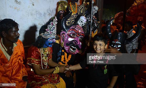 Indian performers dressed as Asura play with a boy in the 'Ravan ki Barat' religious procession in Allahabad The procession was held to mark Dussehra...