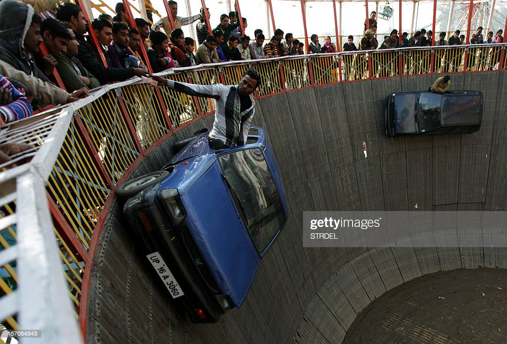 Indian performers ride in cars inside a makeshift wooden cylindrical 'Wall of Death' structure, during the annual farmers fair at Shama Chak Jhiri, some 22kms from Jammu on November 28, 2012. Farmers in huge numbers from all over India gather to pay tribute to the 'Samadhi' or tomb of legendary farmer Baba Jit Mal, popularly known as Baba Jitto who sacrificed his life for the liberation of the farming community. AFP PHOTO/STR