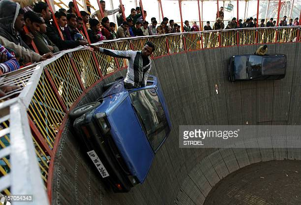 Indian performers ride in cars inside a makeshift wooden cylindrical 'Wall of Death' structure during the annual farmers fair at Shama Chak Jhiri...