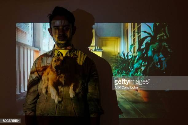 Indian photographer Anurag Banerjee poses for a photograph in front of his art projection during the opening of his photography exhibition inspired...