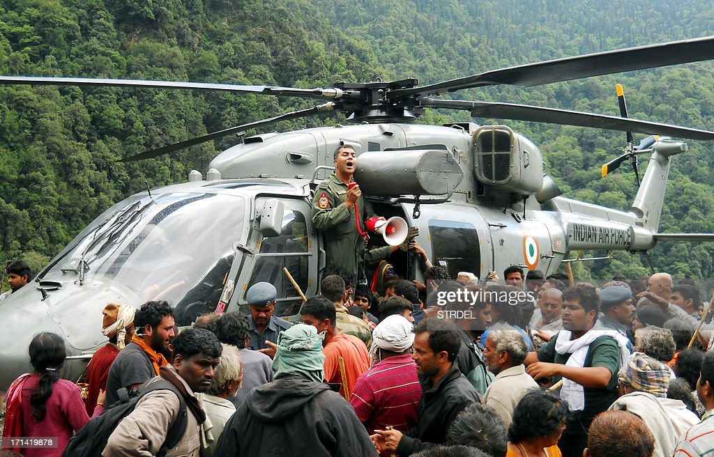 Indian pilgrims wait to board a helicopter to be evacuated after they were stranded because of heavy flooding from near Kedarnath in the state of Uttarakhand on June 24, 2013. Indian priests are planning to cremate hundreds of flood victims on June 24, as heavy rains halted the search for thousands of tourists stranded in the devastated Himalayan region, officials said.