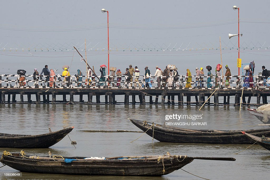 Indian pilgrims walk on a jetty as they head for ferries to cross the Hoogly river on their way to Gangasagar mela in Kakdwip, 110kms south of Kolkata, on January 12, 2013. Devotees will gather at the Gangasagar to take a dip in the ocean at the confluence of the River Ganges and the Bay of Bengal, on the occasion of Makar Sankranti, a holy day of the Hindu calendar considered to be of great religious significance in Hindu mythology. AFP PHOTO/Dibyangshu SARKAR