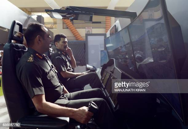 Indian pilots sit in a flight simulator at an aviation stall in the exhibition area on the ithird day of the 11th edition of 'Aero India' a biennial...