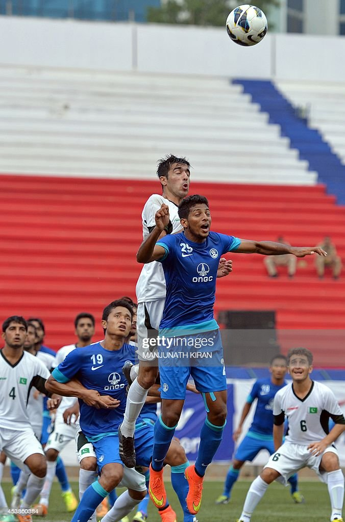 Indian player Joyner Monte Lourenco (centre R, in blue) and Pakistani captain Kaleem Ullah (C, in white) jump to head a ball during a corner kick during their second friendly football match in Bangalore at the Karnataka State Football Association Stadium in Bangalore on August 20, 2014. Pakistan pulled off a surprise 2-0 win over India, with a late goal from Saddam Hussain ensuring a share of the spoils for the visitors in the first football series between the arch rivals for a decade. AFP PHOTO/Manjunath KIRAN