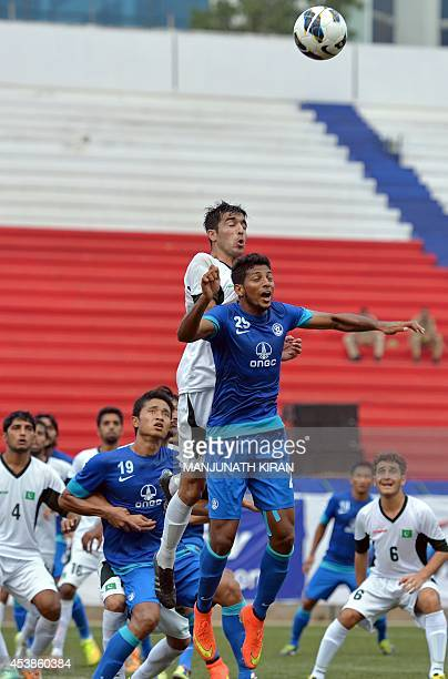 Indian player Joyner Monte Lourenco and Pakistani captain Kaleem Ullah jump to head a ball during a corner kick during their second friendly football...