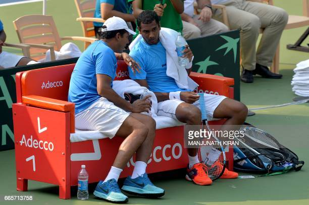 Indian player Ramkumar Ramanathan speaks with his team's nonplaying captain Mahesh Bhupathi during a break in his singles match against Uzbekistan's...