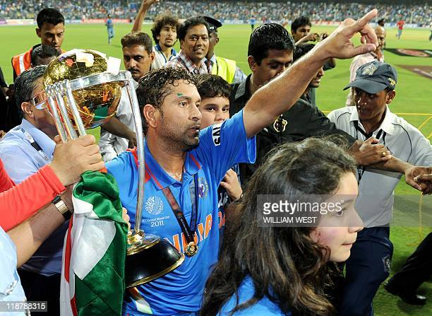 Indian player Sachin Tendulkar carries the trophy with his children Ramesh and daughter Sara after India defeated Sri Lanka in the ICC Cricket World...