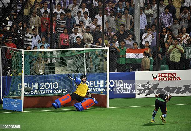 Indian player Saravanjit Singh takes a penalty stroke towards England goalkeeper James Fair during their semifinal field hockey match at The Major...