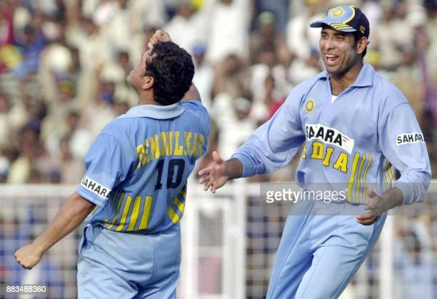 Indian player VVS Laxman runs towards compatriot Sachin Tendulkar to congratulate him for taking the catch of Michael Vaughan of England during their...