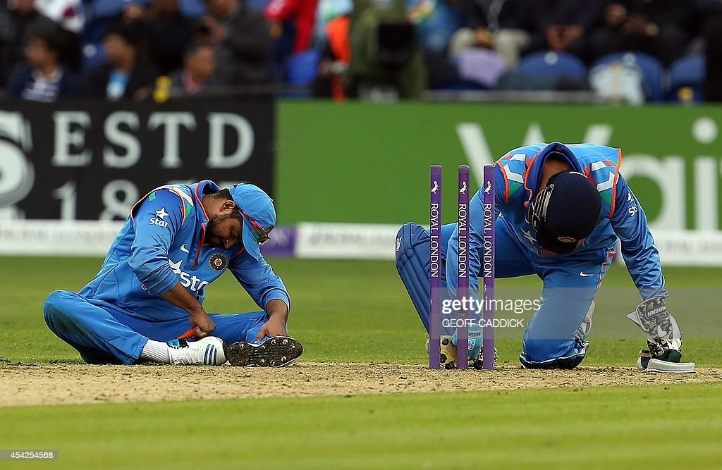 Indian players clean their boots in the second one-day international cricket match between England and India at the Glamorgan County Cricket Ground in Cardiff, Wales on August 27, 2014. India won by 133 runs.