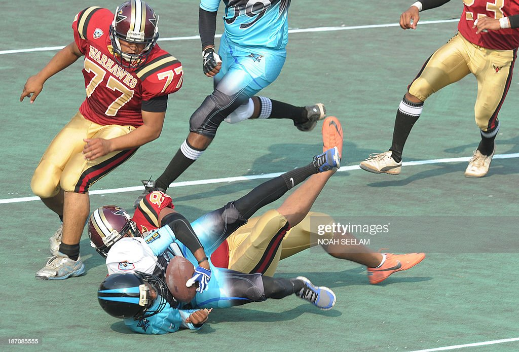 Indian players from the Hyderabad Skykings (blue) and the Bangalore Warhawks (maroon) particiapte in an Elite Football League of India (EFLI) American Football exhibition match at the Begumpet Hockey stadium in Hyderabad on November 6, 2013. American Football will be making its debut in cricket-crazy India with the Elite Football League of India (EFLI) for universities. Ten university teams from across India will vie for the top spot in the first-ever University National League Championship, scheduled to be held on June 2014 in Hyderabad. AFP PHOTO / Noah SEELAM