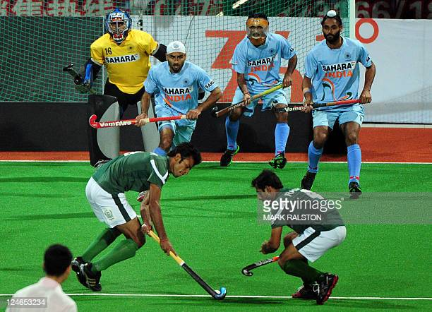 Indian players watch as Pakistan's Muhammad Irfan and Rashid Mwhmood take a penalty corner during their finals match at the first Asian Men's Hockey...