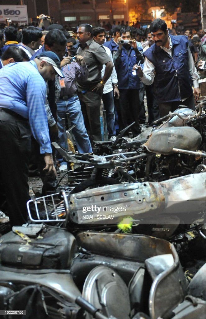 Indian police and forensics officials are pictured at the site of a bomb blast at Dilshuk Nagar in Hyderabad on February 21, 2013. At least 18 people were killed and 52 wounded when bombs ripped through crowded areas of the Indian city of Hyderabad on Thursday in what the prime minister called a 'dastardly act'. AFP PHOTO / Noah SEELAM