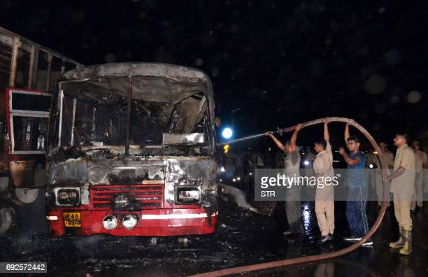 Indian police and recovery personnel douse a bus involved in a collision in Bareilly in India's Uttar Pradesh state on June 5 2017 At least 22 people...