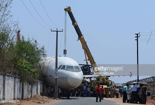 TOPSHOT Indian police and rescue officials gather in front of a disused Air India passenger plane which fell from a ground transporter while being...